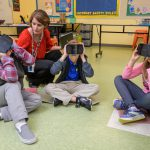 A teacher supports students using virtual-reality headsets to explore new environments.