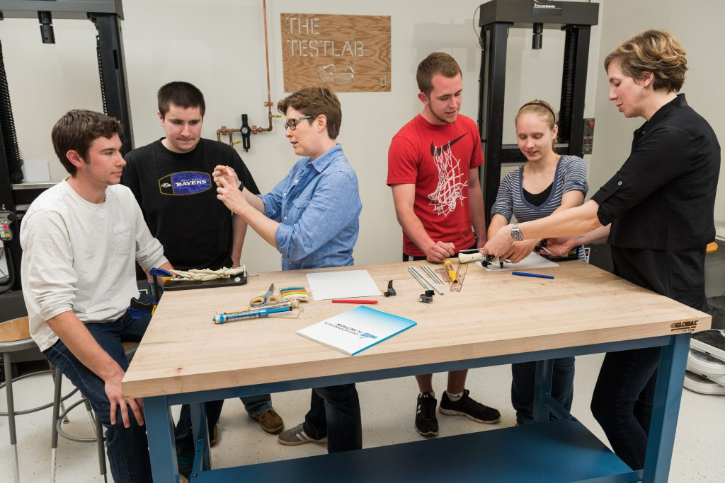 Coaches and UD professors assisting science students to learn engineering concepts.